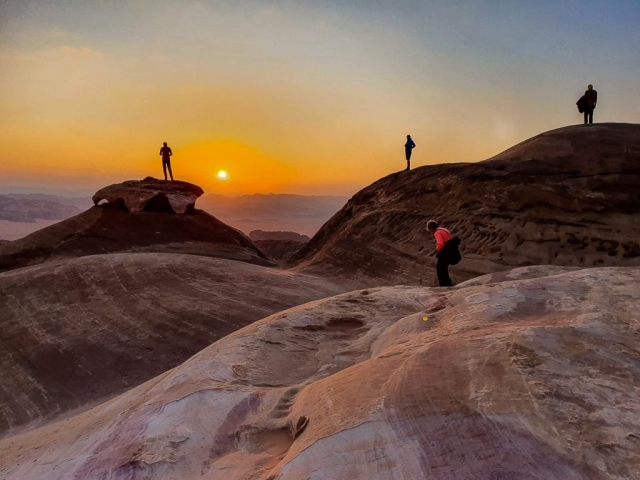 People in the desert at sunset