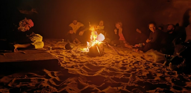 People around the bonfire in the desert at night