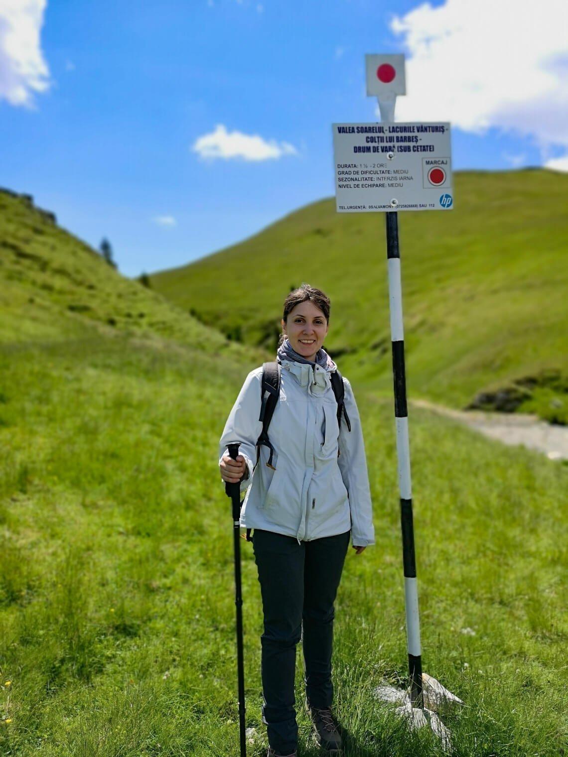Girl standing next to Valea Soarelui placard