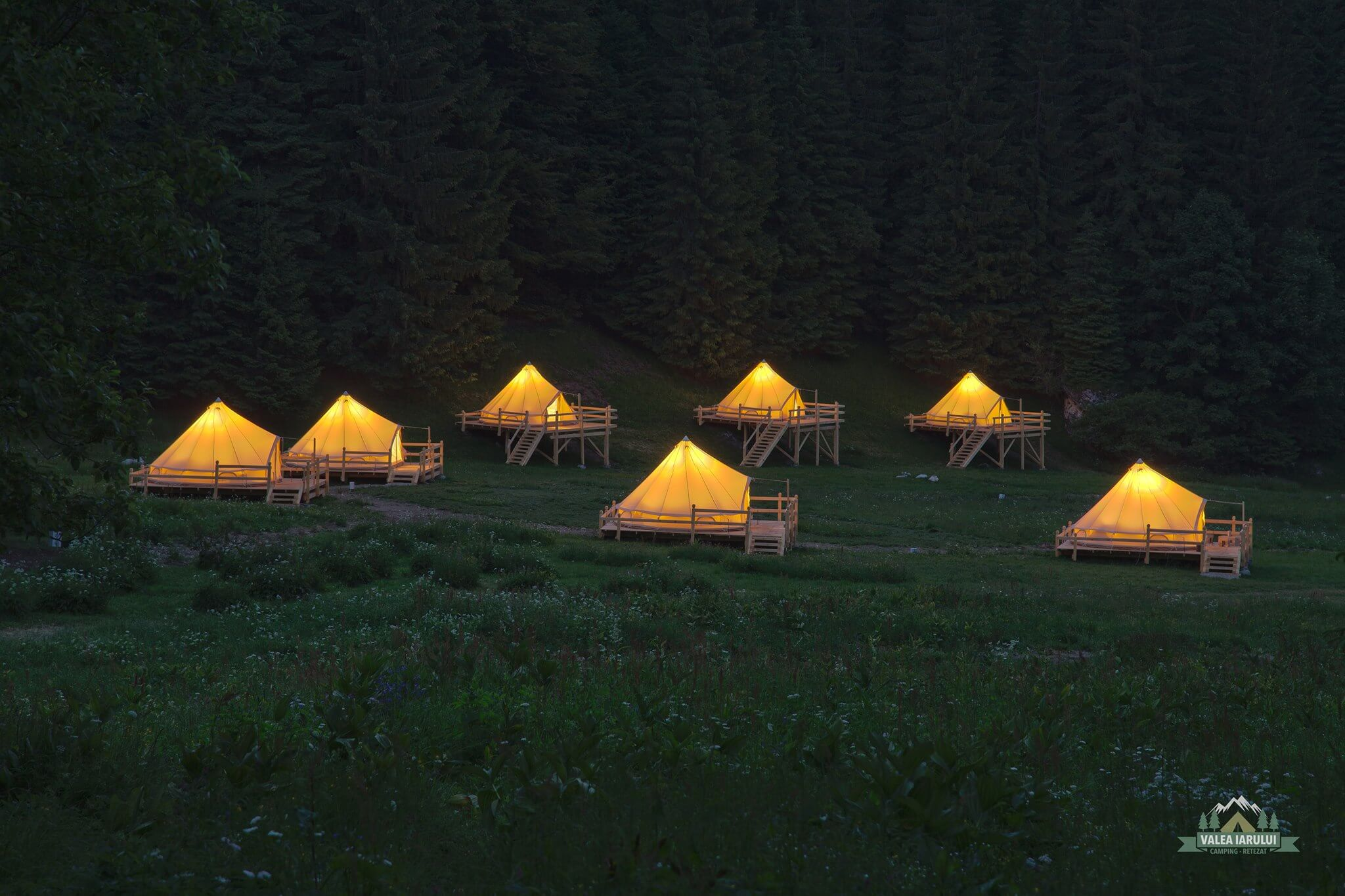 Lighted glamping tents at dusk