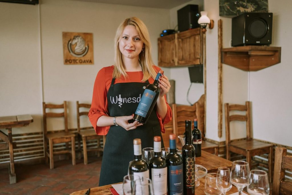 Girl smiling holding wine bottle