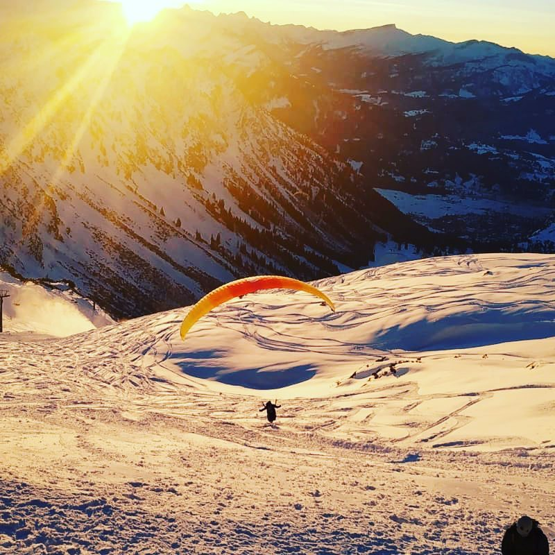 Paraglider flying over the snowy mountains