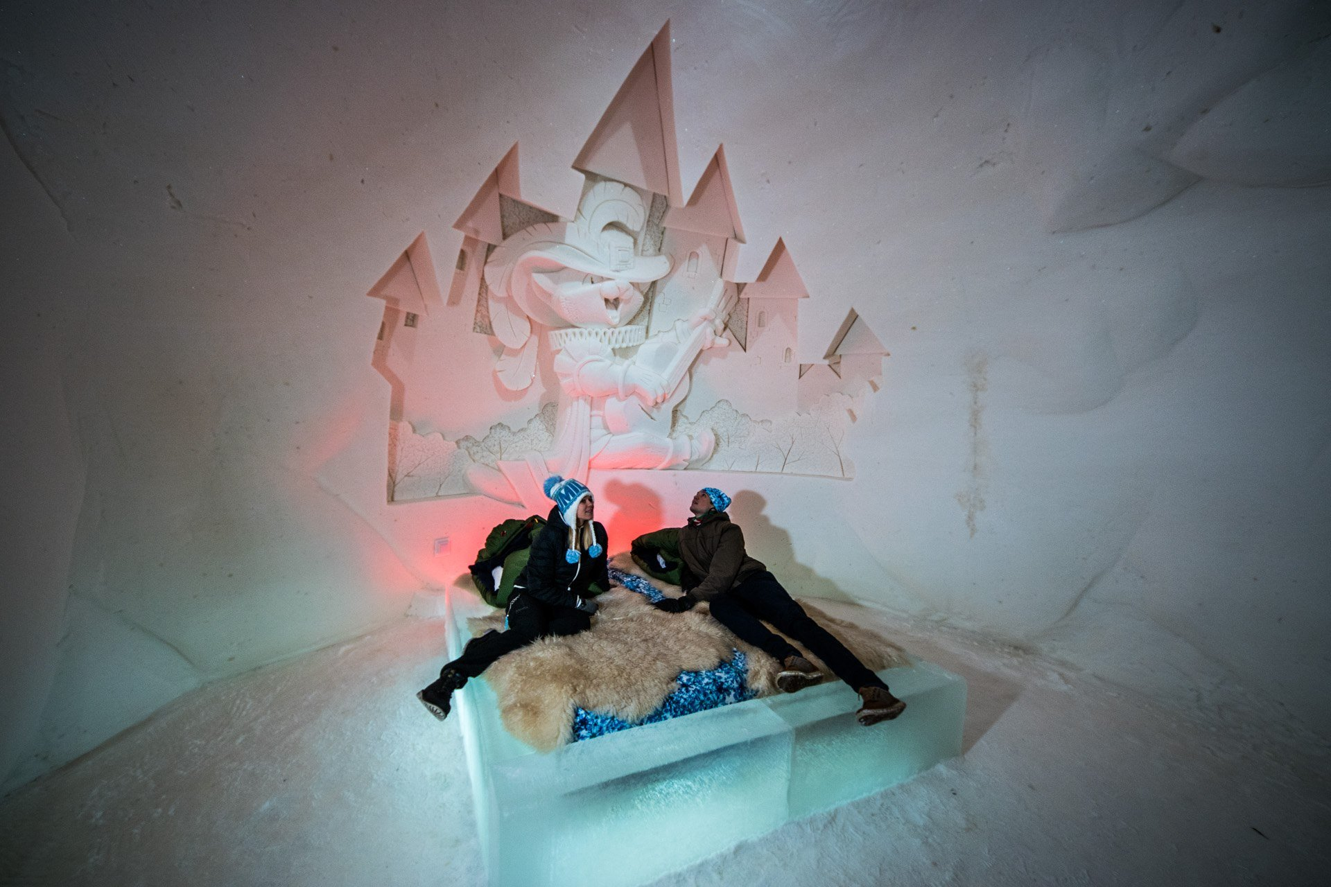 People sitting on a bed in an ice suite