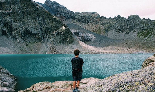 Boy watching mountains by the lake side