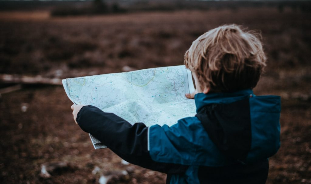 child hiking holding a paper map