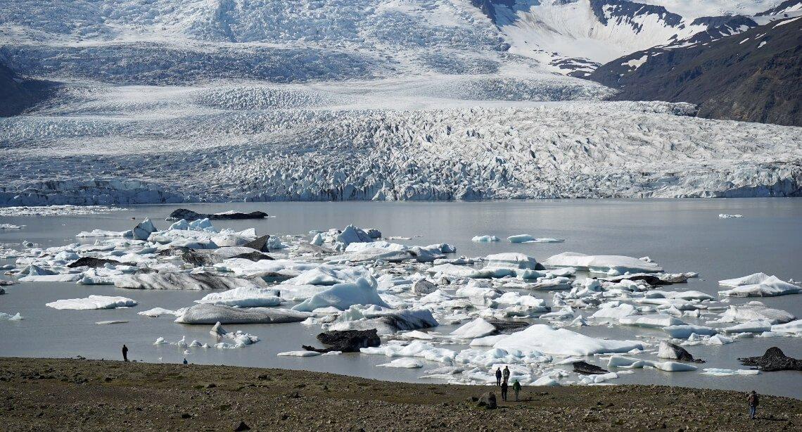 People standing on the shore admiring the Vatnajokull glacier