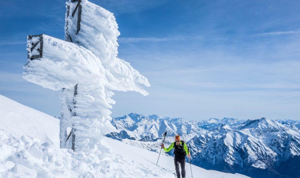Man hiking with trekking poles through the snow