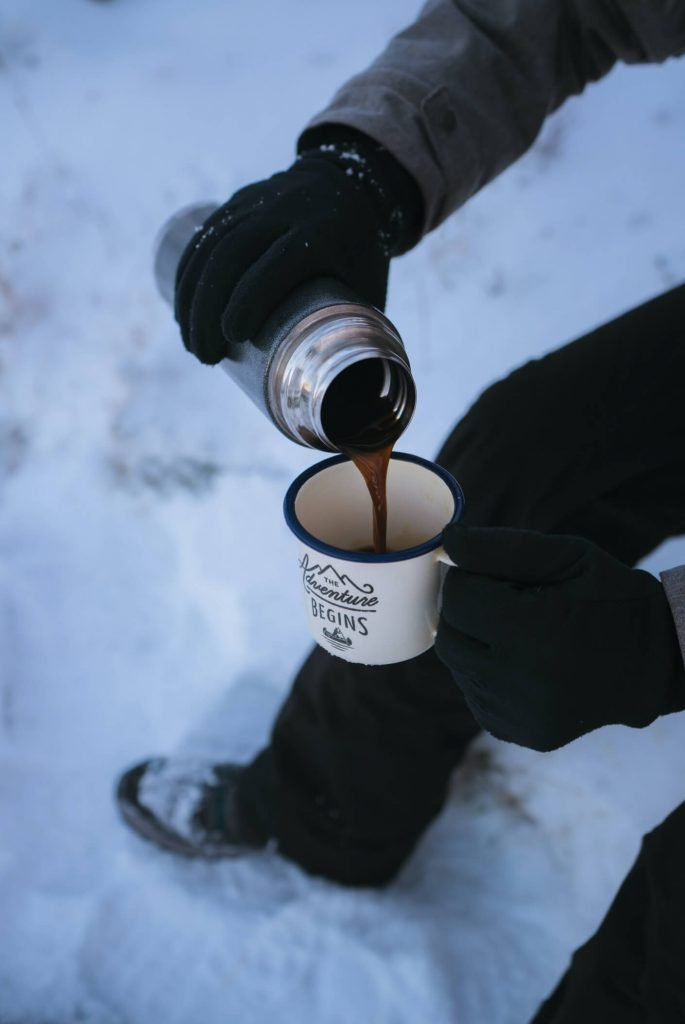 Man pouring tea from thermos on winter hike