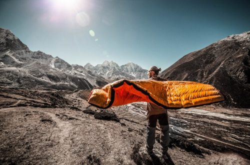 Man in the mountains holding sleeping bag