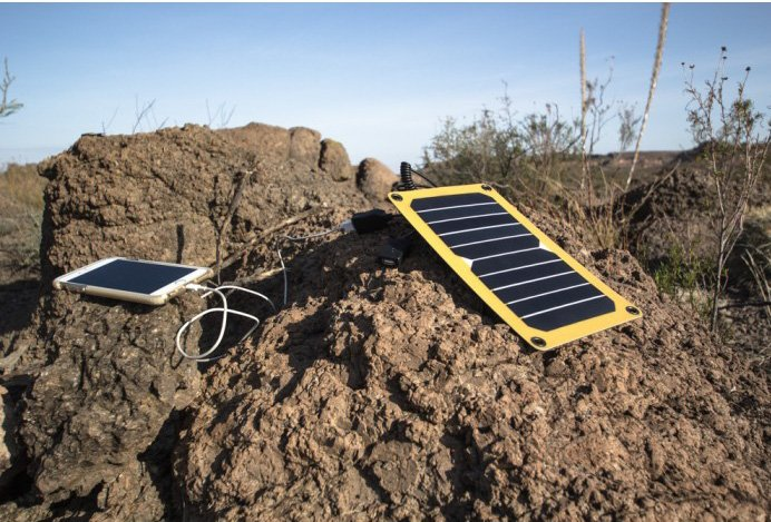portable solar panel on a rock charging a mobile phone