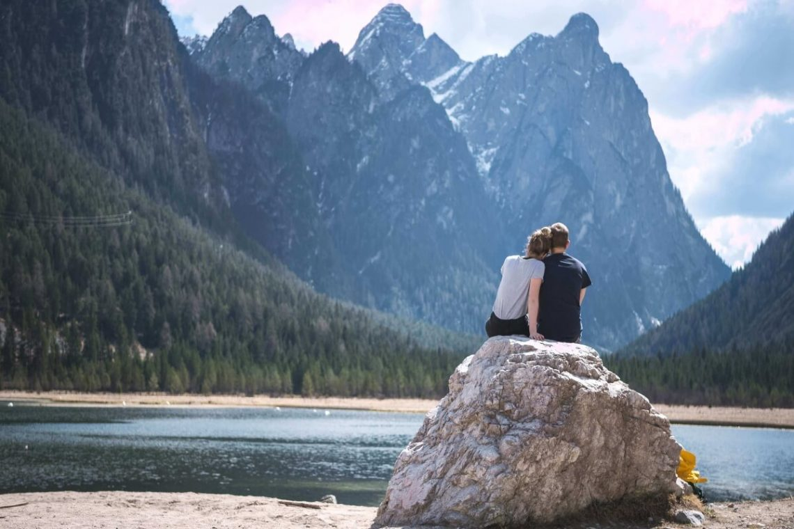 2 lovers sitting on a rock looking at mountain lake
