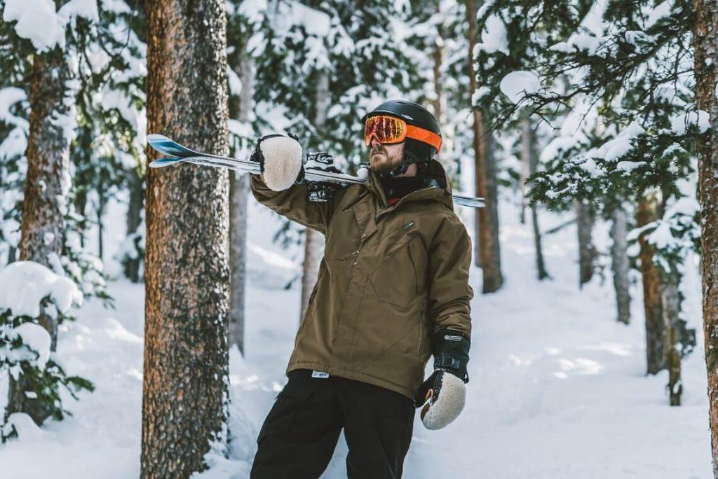 Man holding skis wearing a hardshell jacket